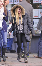 The petite Avril Lavigne bundled up in NYC wearing a large black down jacket with a fur-trimmed hood.