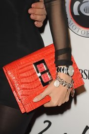Sofia carried an orange statement clutch to brighten up her LBD.