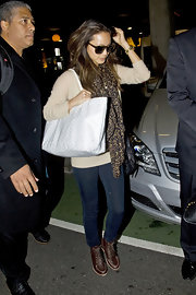 Jamie wears a leopard print scarf with a slouchy sweater and jeans at the airport.