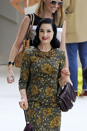 Dita Von Teese complemented her floral printed shift with a rich burgundy Burberry bag.