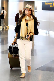 Tiffani Thiessen was spotted in JFK Airport looking sophisticated in white jeans, a loose blouse, and a fringed scarf.