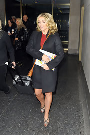Jane Krakowski looked sophisticated in NYC wearing a sleek black coat and a red shift.