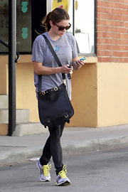 Nikki Reed hit the gym with a polished leather messenger bag in two.