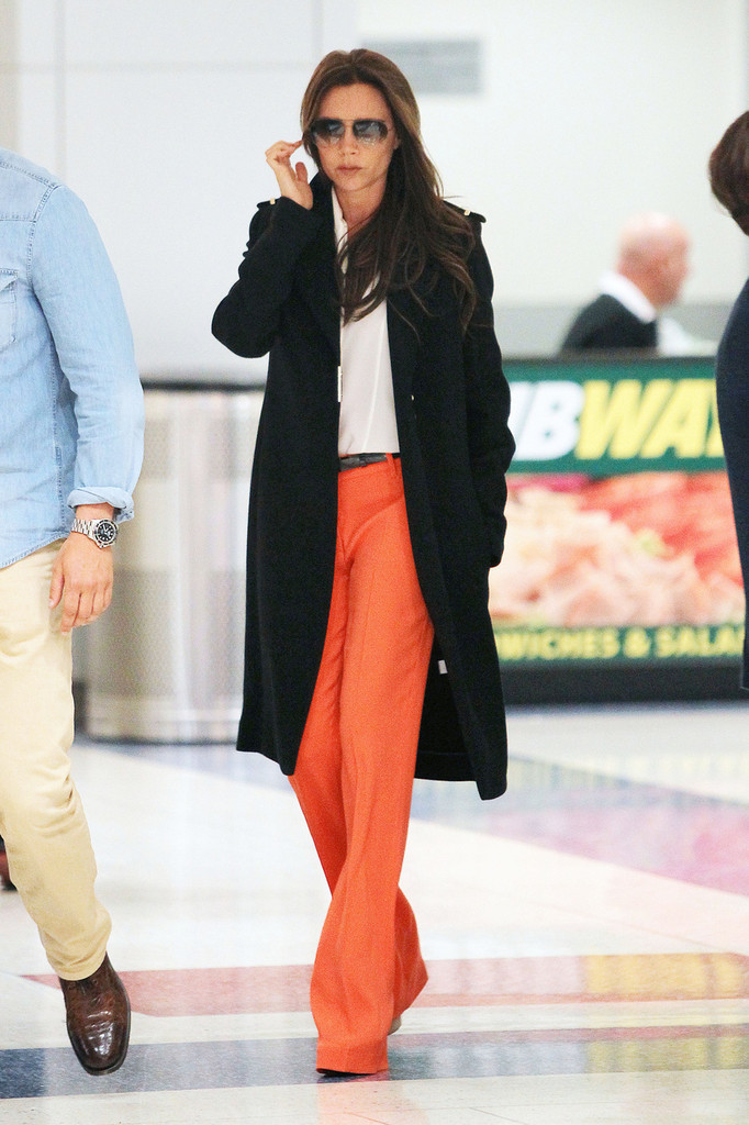 Victoria Beckham, wearing striking orange pants with a white top and black overcoat, seen arriving at JFK Airport in New York City