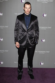 Kellan wears a satin black suit with a rich sheen.