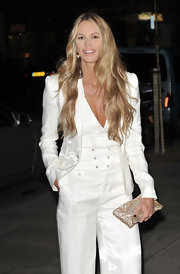 Elle MacPherson added shine to her sophisticated suit with a glittery champagne clutch.