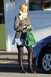 Toni Collette hit the salon in flat knee high boots. She paired the black leather boots with a festive green handbag.