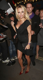 Pamela Anderson showed off her leather clutch while attending a film premiere in London.