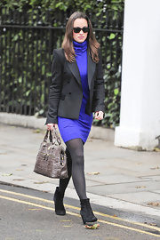 Pippa Middleton looked chic on the way to work in a sweater dress paired with a black blazer and black suede ankle boots.