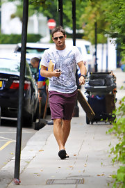Frank wears brightly colored purple shorts with his graphic tee and aviators while out and about in London.  He manages to make this unusual color look so casual.