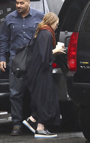 Ashley Olsen teamed her loose black dress with black patent leather sneakers with aqua soles.