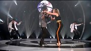 Jennifer Nettles stepped onto the 'Duets' stage in a sporty black one-piece with orange racer-stripes down the legs. A wide gold belt gave the look a Disco touch.
